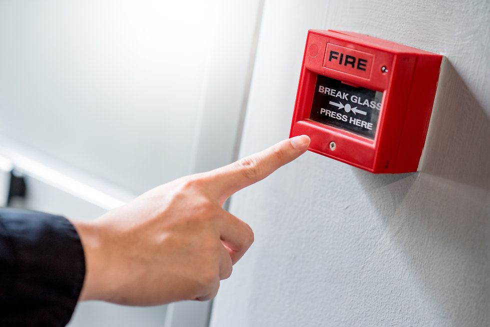 Male hand pointing at red fire alarm switch on concrete wall in office building. Industria