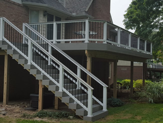 Built in Lake Orion, Michigan.  Trex products used:  enhance clam shell decking select railing cocktail rail and herringbone transcends gravel path fascia