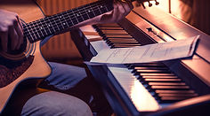man-playing-acoustic-guitar-piano-close-