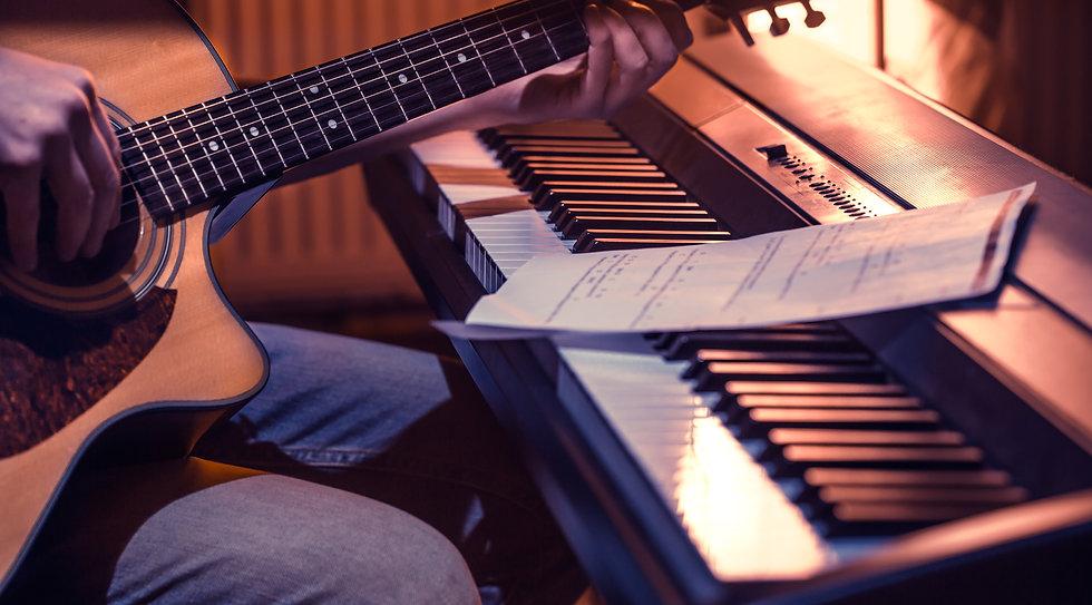 man-playing-acoustic-guitar-piano-close-