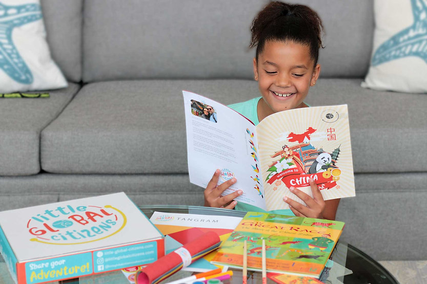 Girl excitedly reads book about China.