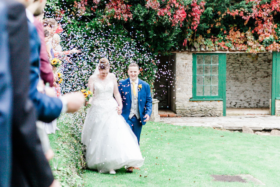Bride and groom at Holbrook Manor wedding being showered in confetti