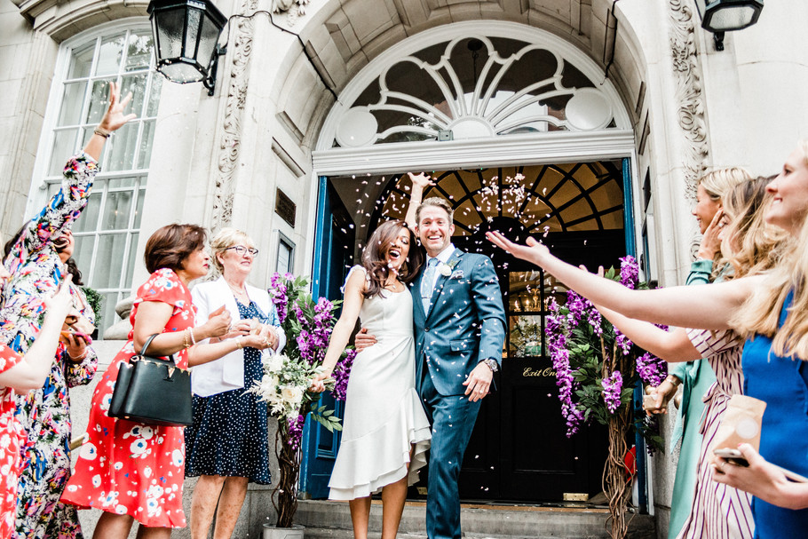 Bride and groom just married at Chelsea Old Town Hall, London, during confetti exit
