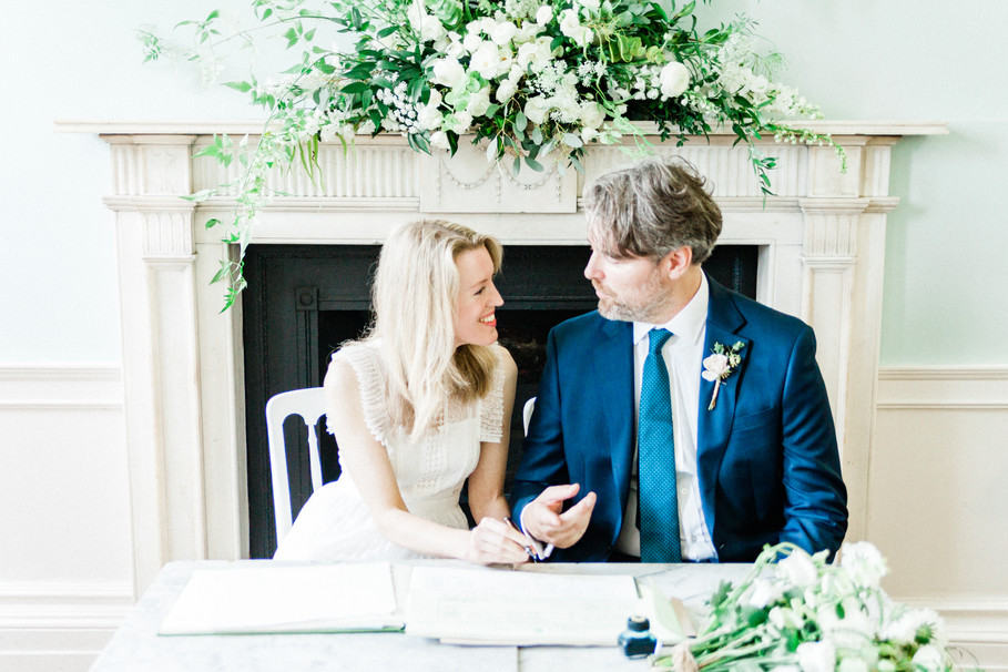 Bride and groom signing the register at their Clissold House wedding