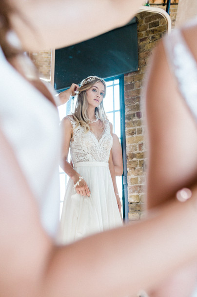Artistic wedding photography shot of bride getting ready in mirror