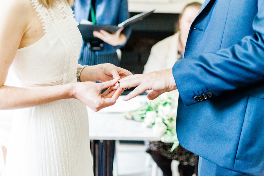 Bride and groom exchanging rings during Clissold House wedding in London