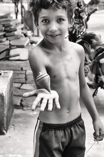 child holding a spinning top on his hand