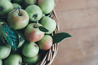a bunch of green apples in a basket.