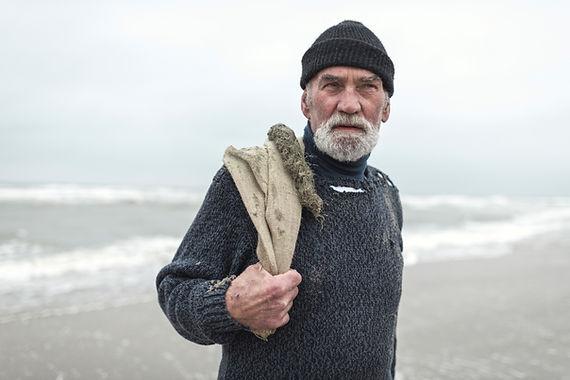 Senior-beachcomber-with-burlap-sack-and-
