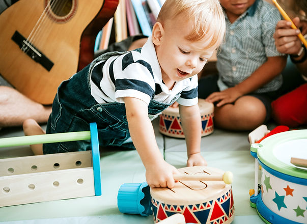 Little%20kid%20playing%20with%20a%20wooden%20drum%20set_edited.jpg