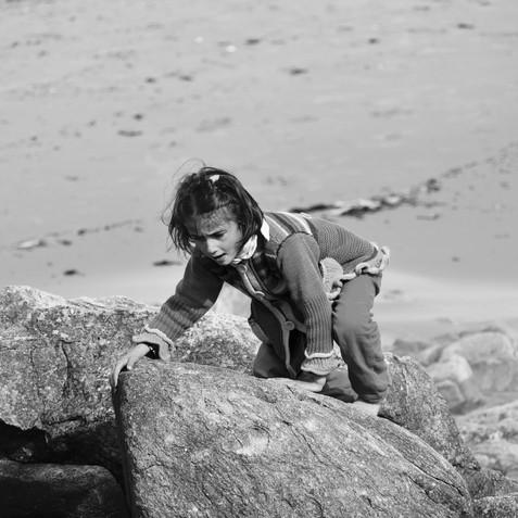 La jeune Fille grimpeuse sur les rochers de la plage