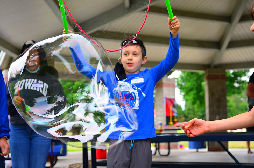 Boy in a blue shirt making a jumbo bubble.