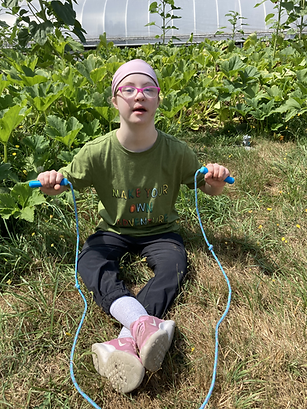 Girl sitting in a garden holding a jump rope.