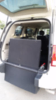 View of the ramp folded up and rear door open in a wheelchair accessibe van