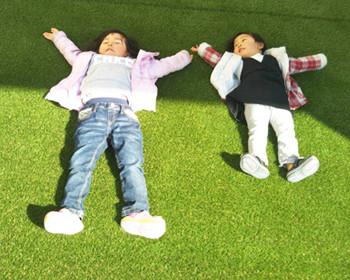 人工芝で子供が寝転ぶ
