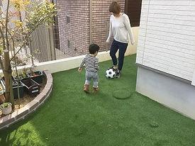 リフォーム後の庭で遊ぶ親子.JPG