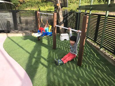 人工芝の上の鉄棒で遊ぶ子供達