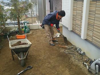 土を掘る男性