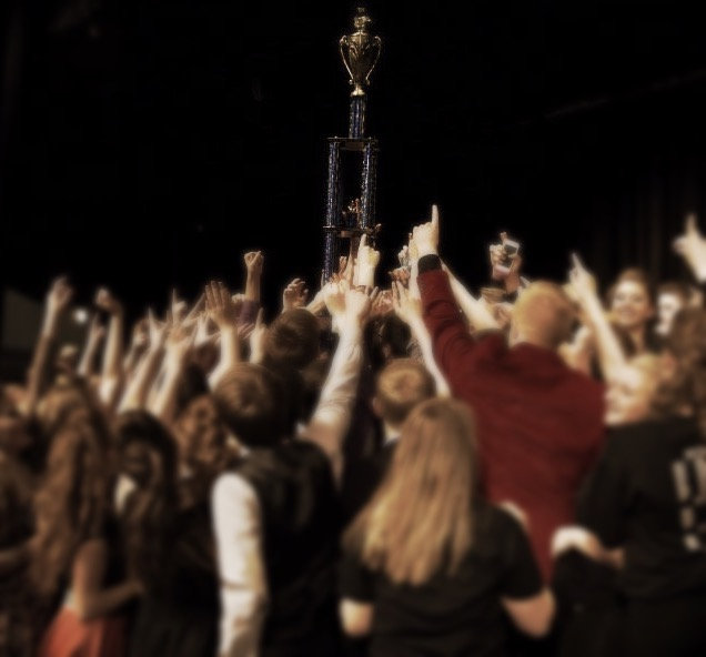 Background photo of Centennial Show Choir students celebrating with a trophy