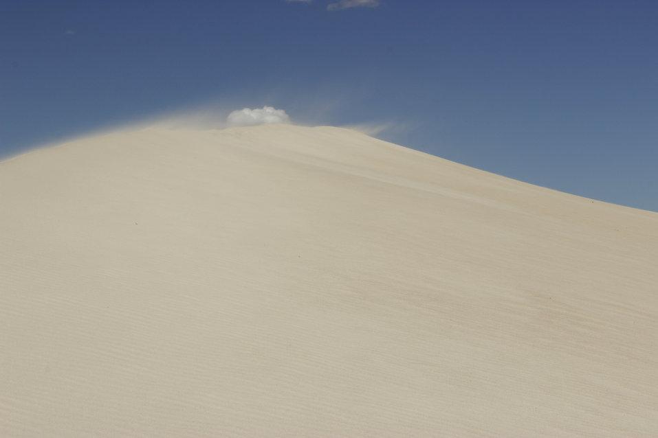 Sanddüne mit Wolke und blauem Himmel