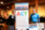 ACT board member Elizabeth Edgerton and ACT student pose by a sign with ACT's logo and mission