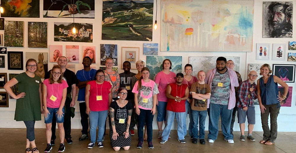Fifteen students, two volunteers, and two ACT staff members stand in a line in front of a gallery wall filled with paintings and photographs