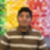 Richard Maya-Vazquez headshot in front of colorful green, yellow, and red background