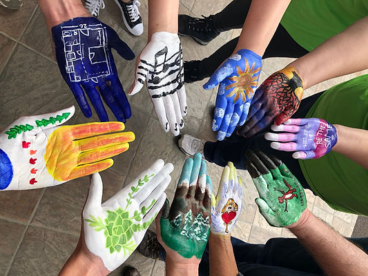 A variety of colorfully painted hands are held palm up for the camera