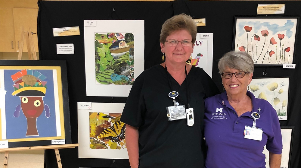 Two doctors standing in front of a display board filled with student-made artwork