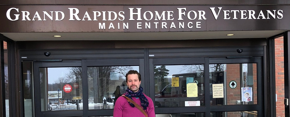 "Young white man (Steven Edelman) wearing a dark blue scarf and a magenta sweater stands and smiles at the front entrance of a building, beneath a large sign that says ""Grand Rapids Home For Veterans Main Entrance"""