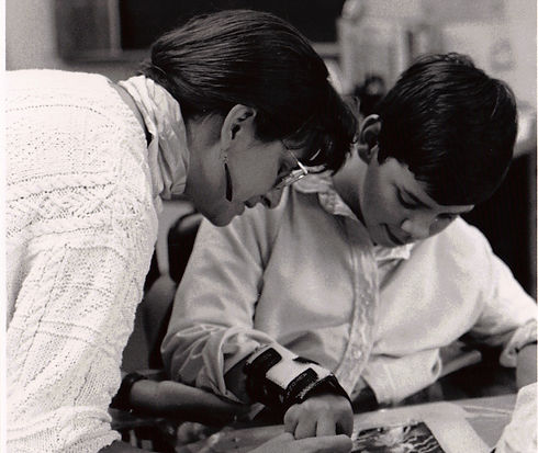 A black and white image of a teaching artist works with a student