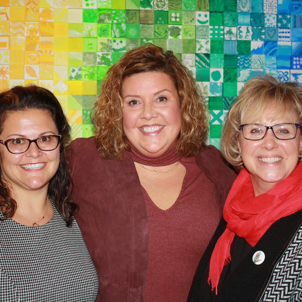 Three white women smile in front of a rainbow-painted wall.