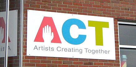 A sign on the brick wall of ACT's Monroe studio space featuring the colorful Artists Creating Together logo