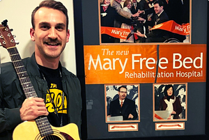 """Young white man (John Nowak) holds up an acoustic guitar and smiles next to a poster with the title """"Mary Free Bed Rehabilitation Hospital"""""""