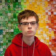 Jacob Whitsell headshot in front of colorful green, yellow, and red background