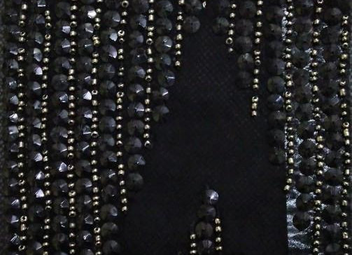 Rows of matte black sequins on hand-embroidered fabric