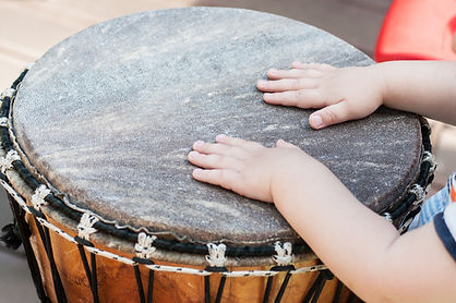 closeup of baby hands on african drums