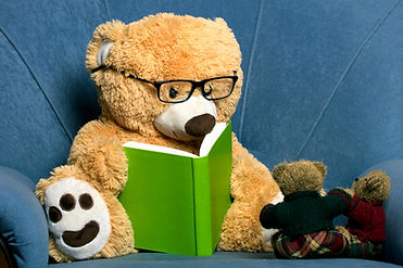 teddy bear with glasses reading a book.j