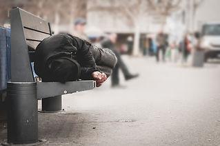 Poor homeless man or refugee sleeping on