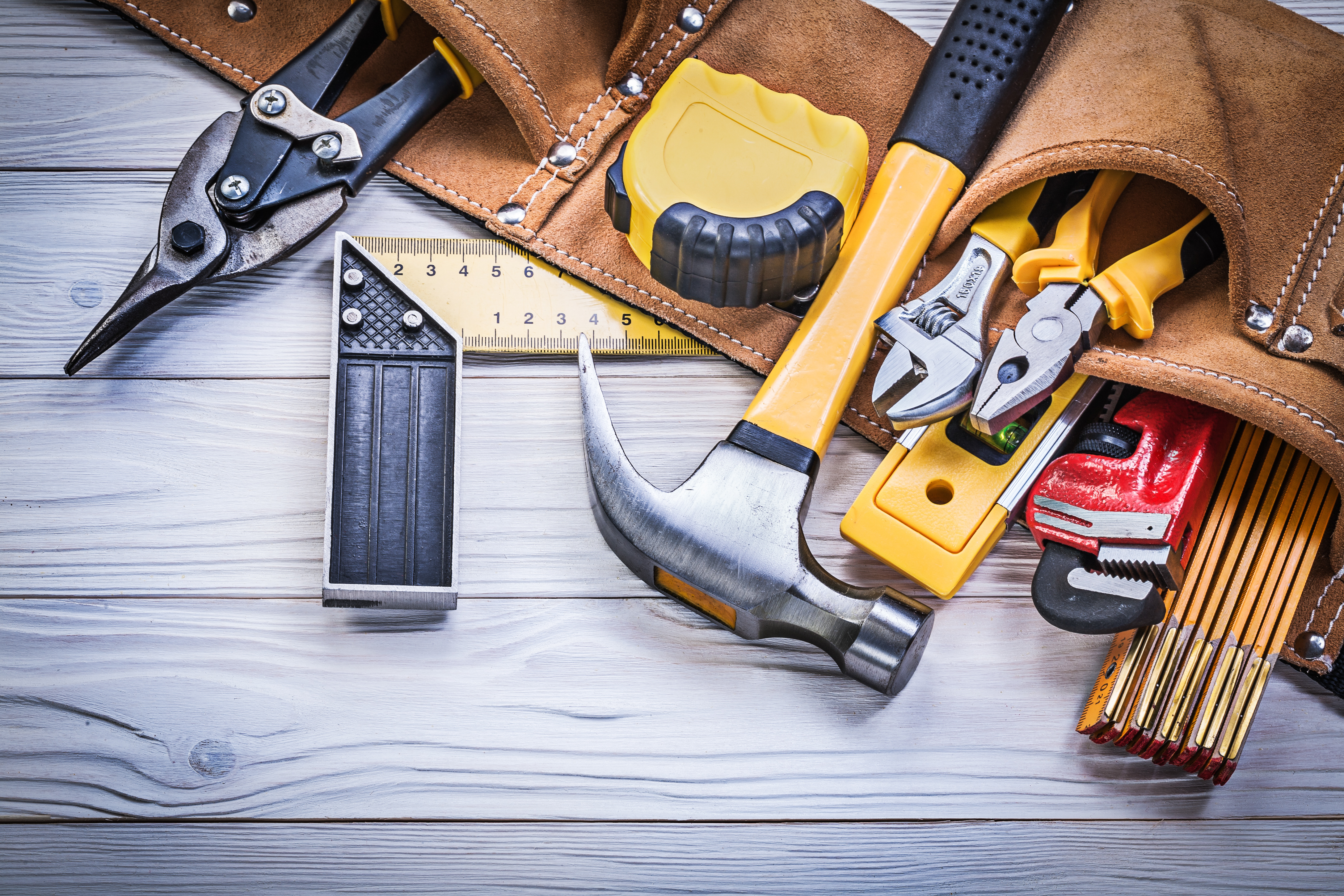 Leather tool belt with construction tooling on wooden board maintenance concept