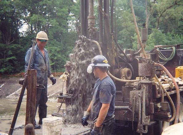 Photograph of an all-Terrain drilling crew working on BH1, July 2003.