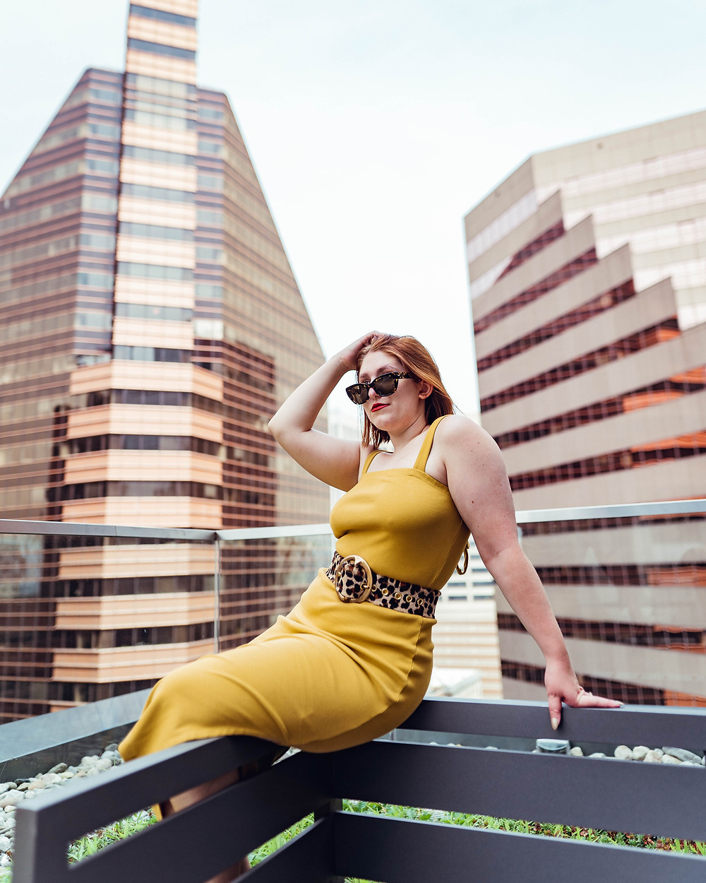 Taylor sits on balcony with city views of Baltimore City wearing wearing a yellow dress.