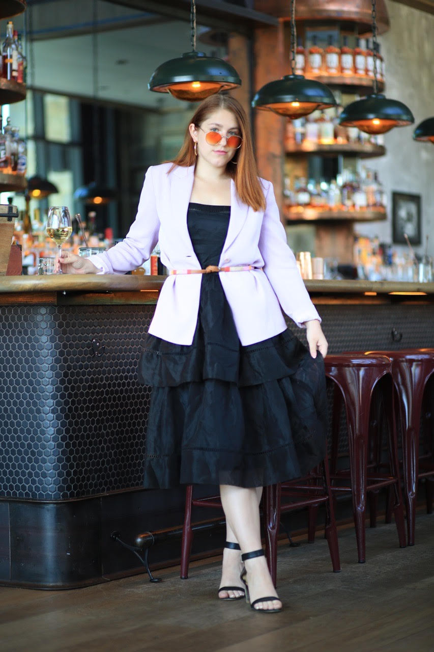 Redheaded girl stands infront of bar wearing a belted lilac blazer over a black midi-dress.