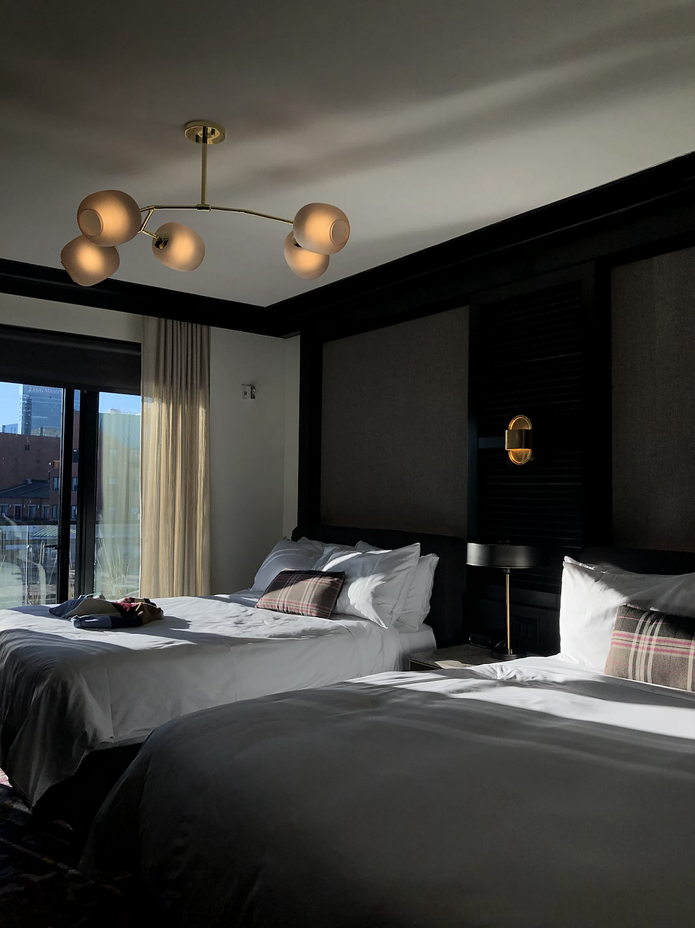 Natural light pours into hotel room and hits the two queen beds.