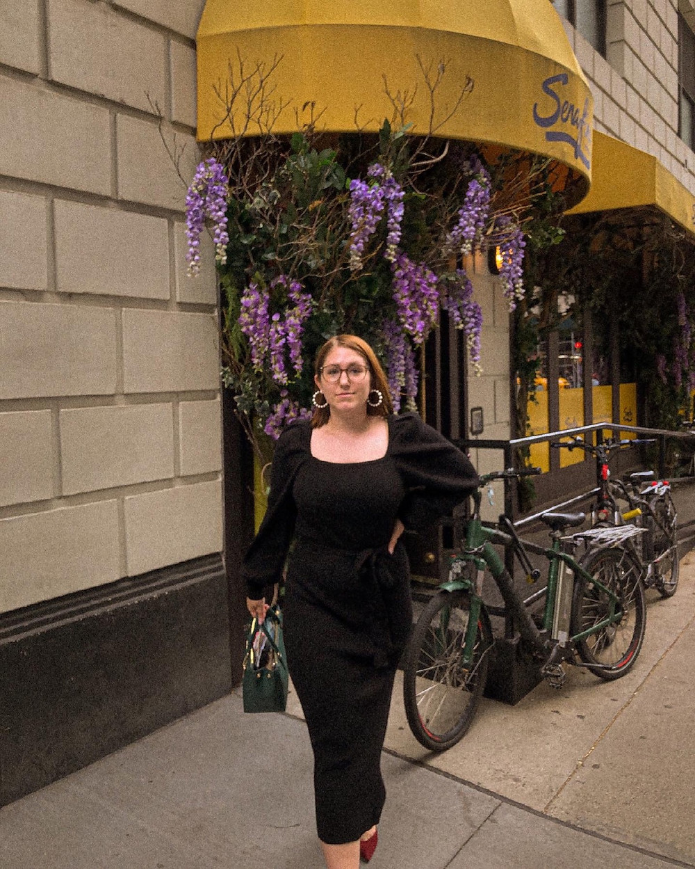Taylor outside restaurant with purple vine flowers, wearing a black maxi dress with square neckline..