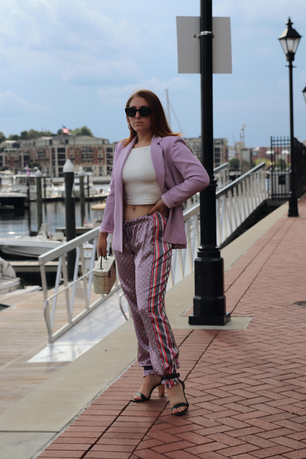 Redheaded girl stands infront of water wearing a  lilac blazer with a white crop top and printed, silk pajama pants.