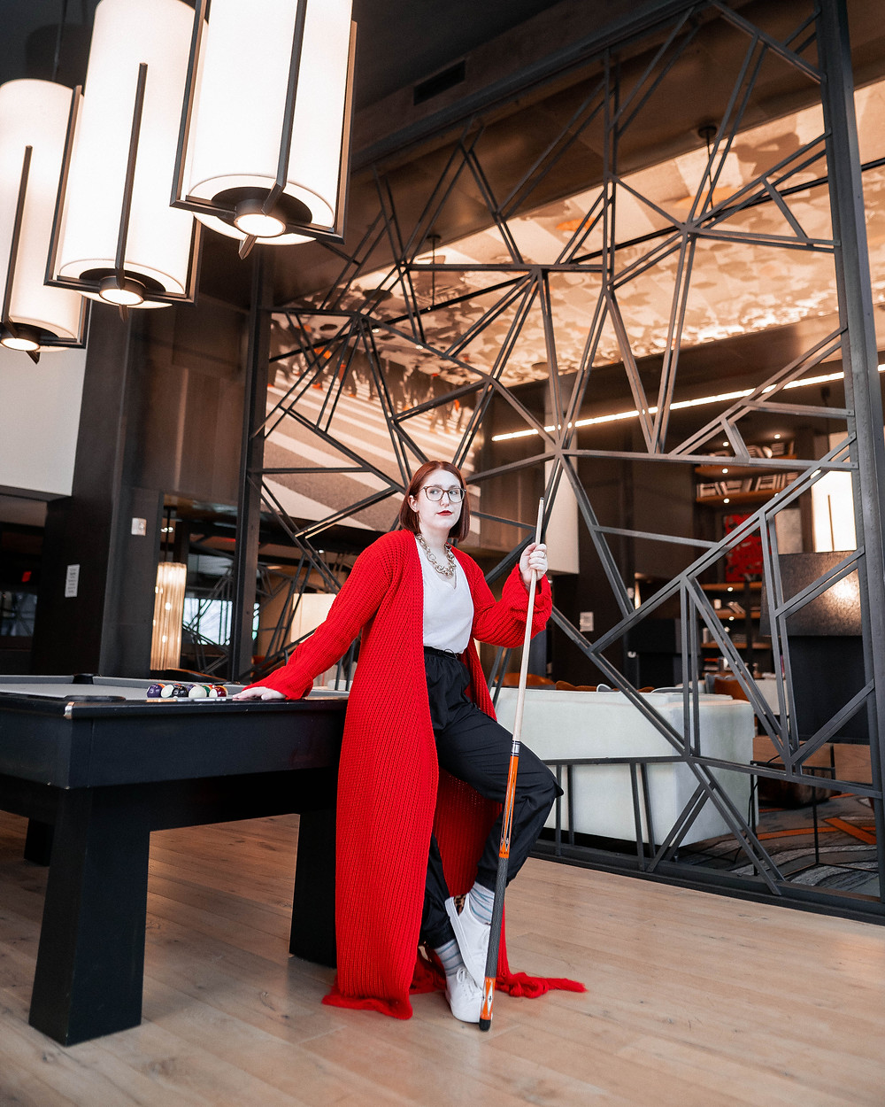 Taylor wearing a red maxi cardigan as leans against the pool table in Anthem House's community space.