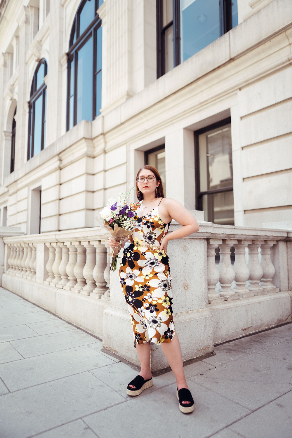 Taylor wearing patterned slip dress and holding flowers outside a building in Washington, DC.