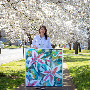 Hannah Lane under cherry blossoms with framed Stargazers painting