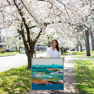 Hannah Lane under cherry trees with one of her original paintings